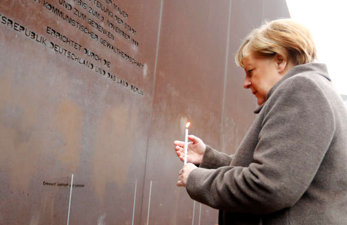 German Chancellor Angela Merkel lights a candle in front of a Memorial in honor of the victims of communism on 9 November 2019 in Berlin.
