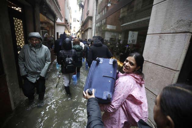 I turisti portare i bagagli nelle strade dove il livello dell'acqua è montato a un livello eccezionale, il 12 novembre.