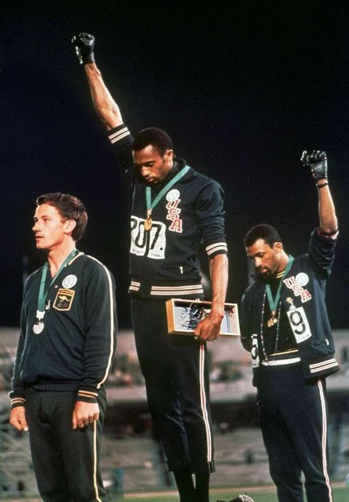 Tommie Smith (médaille d'or,au centre) et John Carlos (médaille de bronze), le poing ganté levé sur le podium du 200m des Jeux olympiques, à Mexico, le 16octobre1968.