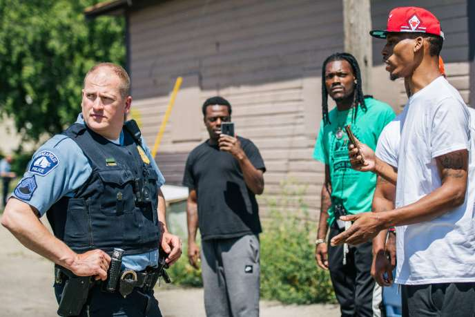 A people exchange with a police officer on a scene of crime, in Minneapolis (Minnesota), June 16.