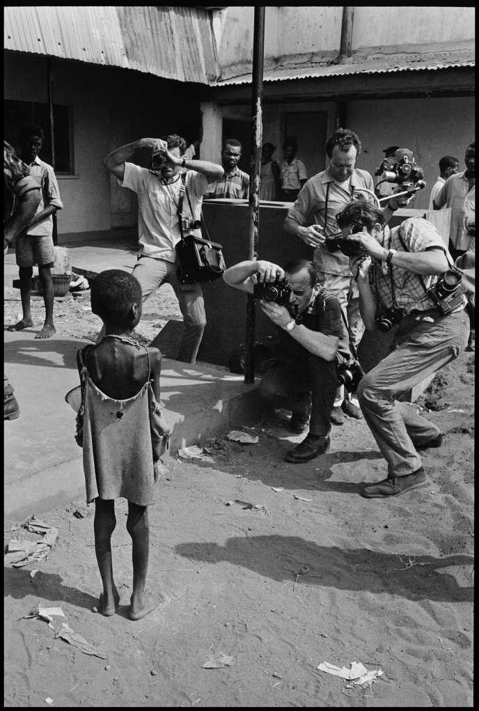 Des photographes occidentaux prennent en photo un enfant qui souffre de malnutrition à cause de la guerre du Biafra, à Owerri, en 1970.