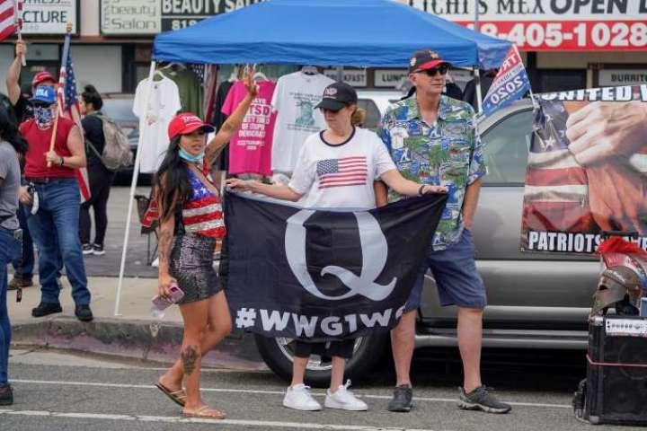Une femme brandit un drapeau«Q» à LosAngeles, le 21août 2020, lors d'un rassemblement pro-Trump.