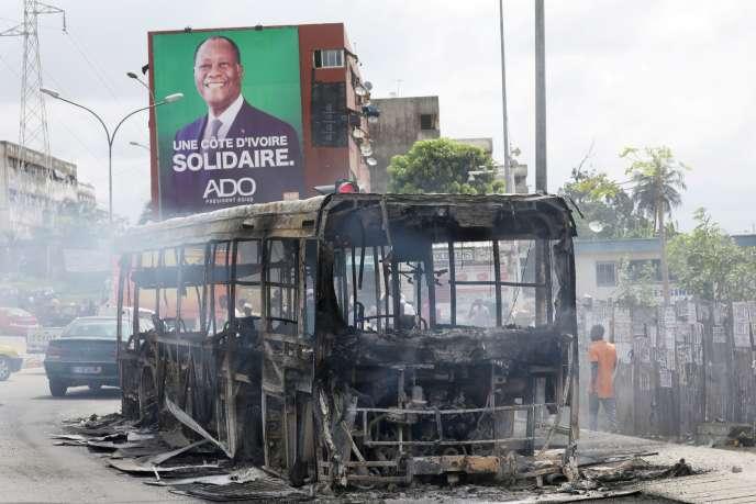 Un bus incendié devant une affiche de campagne du président Alassane Ouattara, à Abidjan, le 19 octobre.