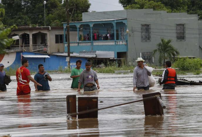 Des habitants dans une rue submergée de la ville de La Lima, au Honduras, le 18 novembre.