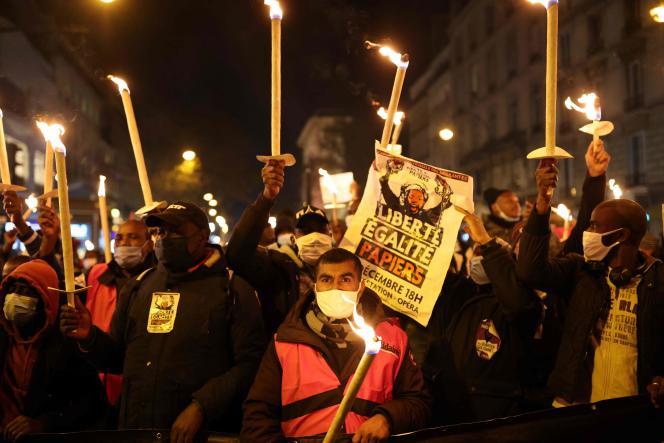 Des manifestants brandissent des bougies et des pancartes lors d'une manifestation pour la régularisation des sans-papiers, à l'occasion de la Journée internationale des migrants, le 18 décembre, à Paris.