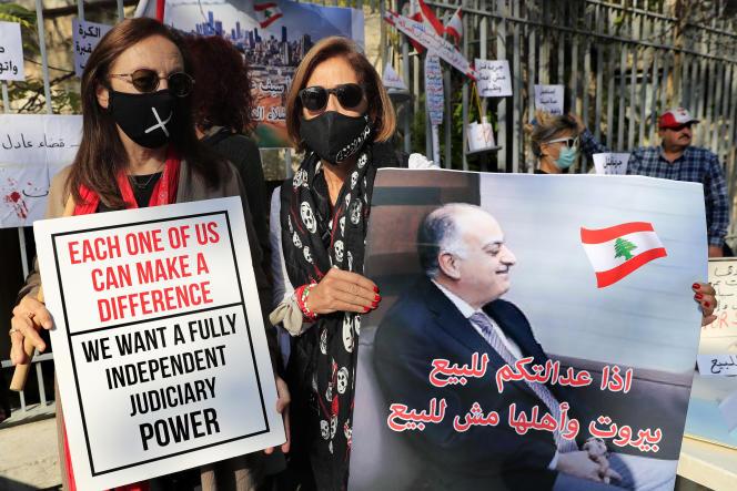 Un Libanais tient une pancarte montrant un portrait du juge libanais Fadi Sawan chargé de l'enquête sur l'explosion au port de Beyrouth, avec écrit en arabe: « Si votre justice est à vendre, Beyrouth et son peuple ne sont pas à vendre», lors d'une manifestation devant le palais de justice, à Beyrouth, le 3 décembre 2020.