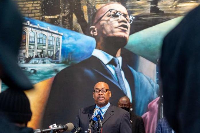 Conférence de presse à New York, samedi 20 février, devant un portrait de Malcolm X, de Reggie Wood, membre de la famille de Ray Wood, le policier qui a écrit une lettre accusant les forces de l'ordre de complicité dans le meurtre de l'activiste afro-américain.