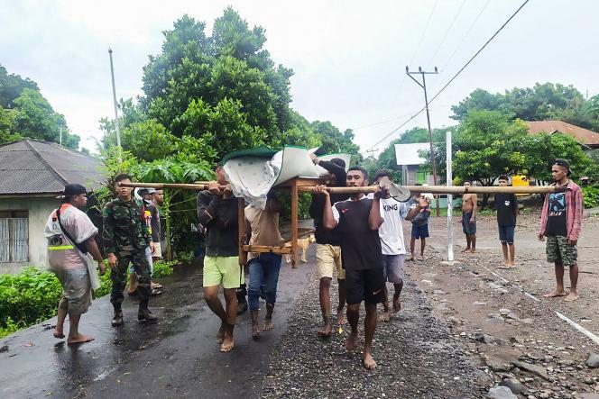 Les villageois portent le corps d'une victime après les inondations à Lembata, dans l'est de Florès, le 5avril.