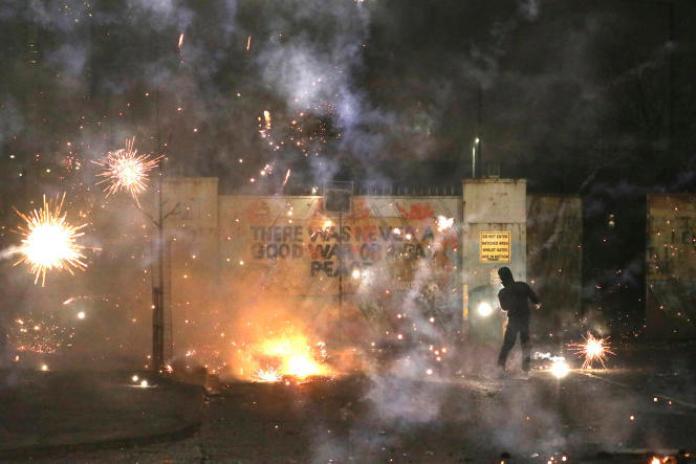 Des émeutiers nationalistes et loyalistes s'affrontent devant mur de la paix, sur Lanark Way, à Belfast, en Irlande du Nord, le 7 avril.