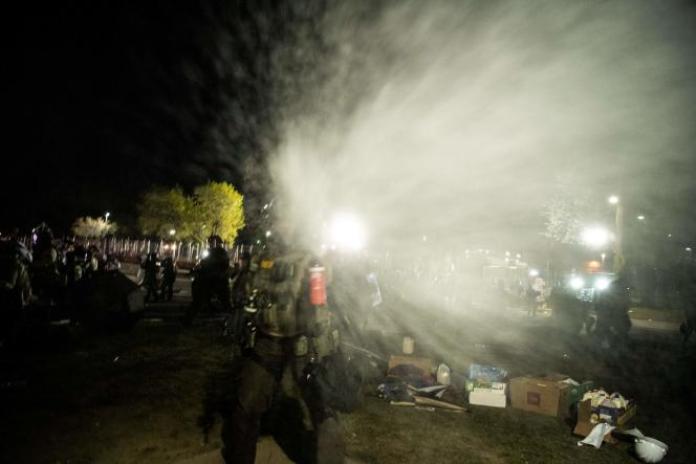 Les policiers font usage de gaz poivre sur plusieurs journalistes, devant le commissariat deBrooklyn Center (Minnesota), vendredi 16 avril.