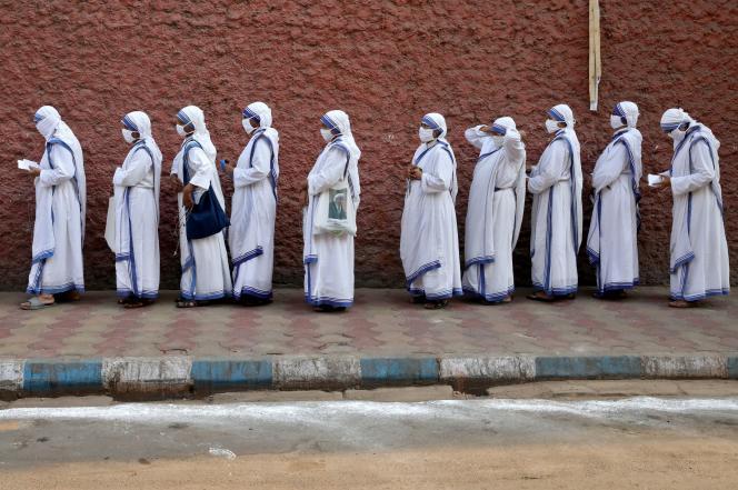 Des soeurs catholiques font la queue pour voter en portant un masque, à Calcutta, le 29 avril.
