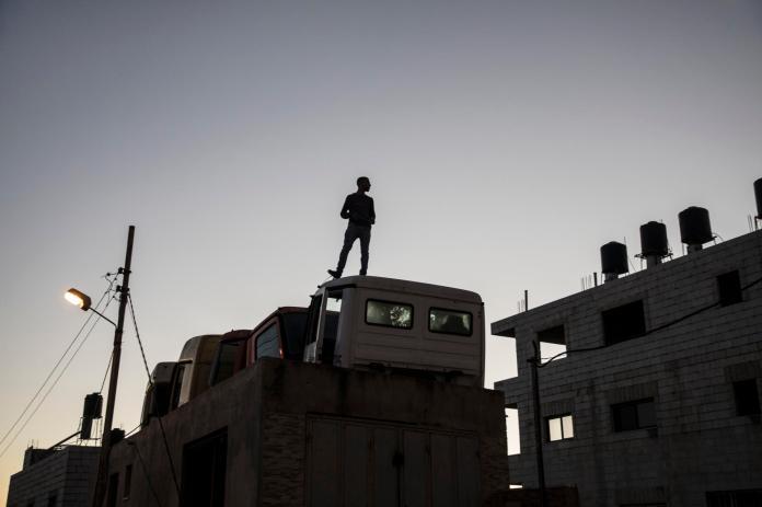 Un jeune Palestinien guette les forces armées israéliennes au-delà du barrage aménagé à l'entrée du village de Silwad (Cisjordanie), sur la route pour Ramallah, le 15 mai 2021.