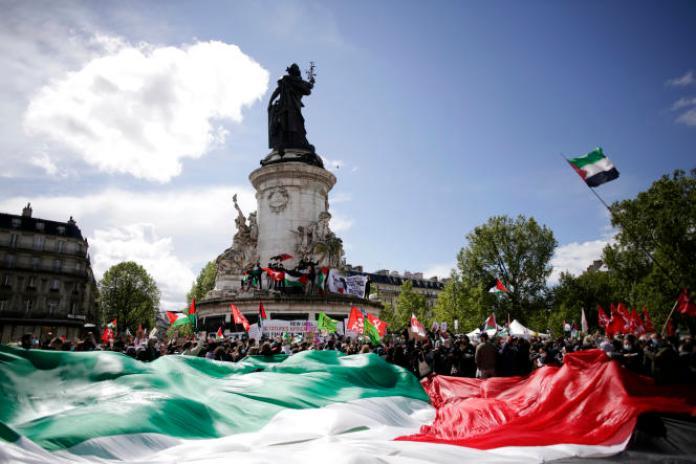 Des manifestants tiennent un drapeau palestinien géant à Paris, le 22mai2021, lors d'un rassemblement en soutien aux Palestiniens.