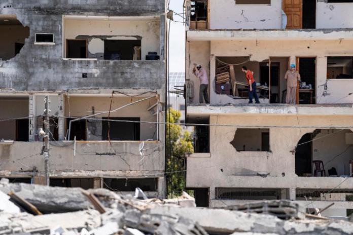 Des personnes travaillent dans des immeubles d'habitation endommagés, dans la ville de Gaza, samedi 22mai2021.