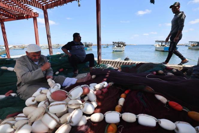 Des pêcheurs palestiniens réparent leurs filets avant de prendre la mer dans le port principal de la ville de Gaza, le 22mai2021, après la levée de l'interdiction de pêcher à la suite du cessez-le-feu entre Israël et les militants palestiniens dans l'enclave sous blocus israélien.