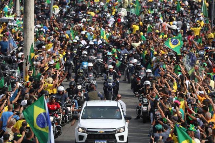 Jair Bolsonaro salue ses partisans,à Rio de Janeiro, le 23 mai 2021. Le président brésilien a parcouru 33 km à moto entouré d'un peloton de motards.