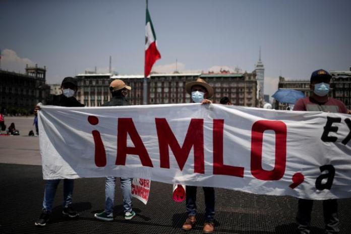 Des élèves tiennent une banderole indiquant «AMLO» (pour Andres Manuel Lopez Obrador, le nom du président mexicain), lors d'une marche contre la réouverture des écoles au Mexique, dans le Zocalo, à Mexico, le 24 mai 2021.