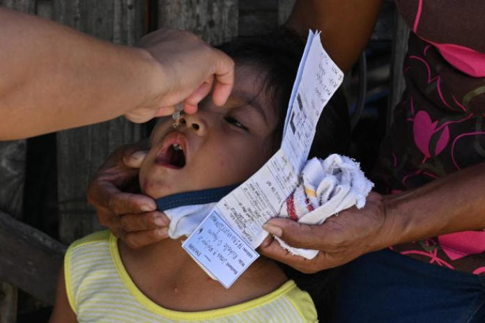 Un agent de santé municipal applique des gouttes d'un vaccin contre la polio à un enfant, à San Jose Del Monte, dans la province de Bulacan, au nord de Manille,le 21 septembre 2020.