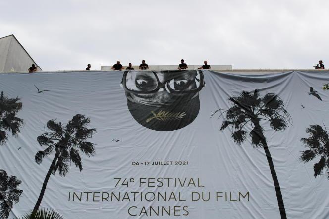 Installation de la toile géante de l'affiche officielle mettant en scène Spike Lee sur la façade du palais des Festivals à Cannes, le 4 juillet 2021.
