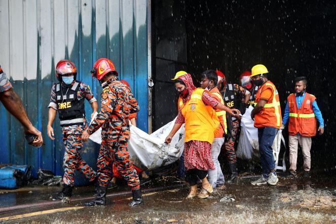 Des secouristes portent les corps trouvés dansl'usine incendiée d'Hashem Foods, près de Dacca, au Bangladesh, le 9 juillet 2021.