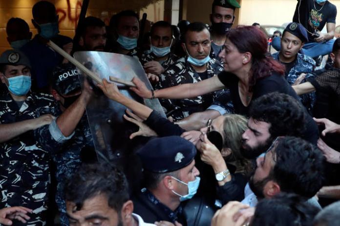 Des proches de victimes de l'explosion du port de Beyrouth s'opposent à la police qui garde l'entrée du domicile du ministre de l'intérieur par intérim, le 13 juillet 2021.