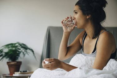 woman in bed drinking water to stop post-nasal drip