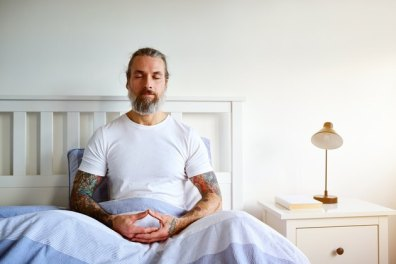Mature man sitting peacefully on bed