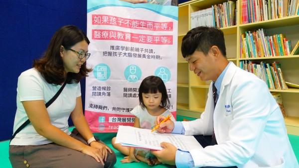陳宥達(右)鼓勵父母可以從一天五分鐘做起,陪伴孩子閱讀。(新北市立圖書館汐止分館提供)