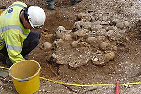 Gruesome: An archaeologist sifts through the remains of the mass grave