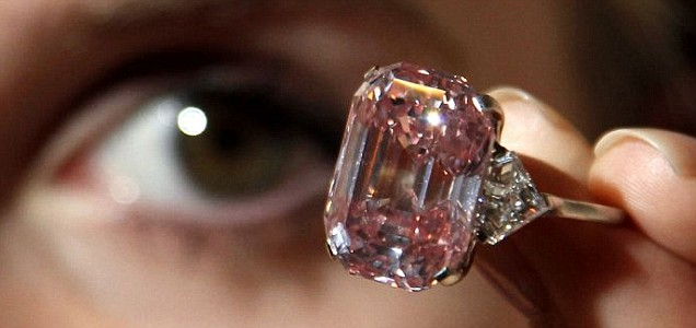 A Sotheby's employee poses with the 24.78-carat fancy intense pink diamond
