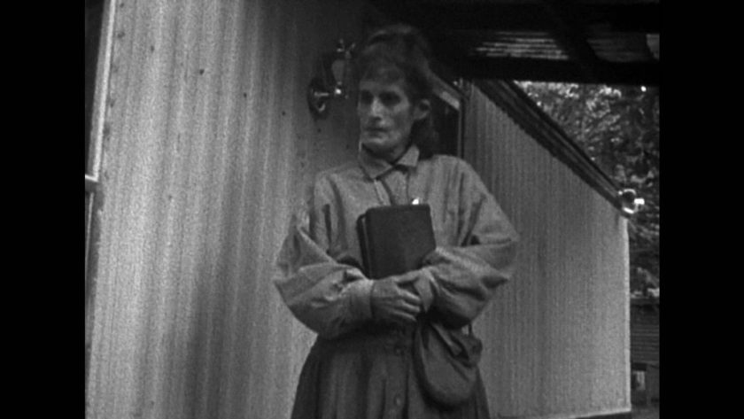 Black and white image shows old woman holding book against chest.