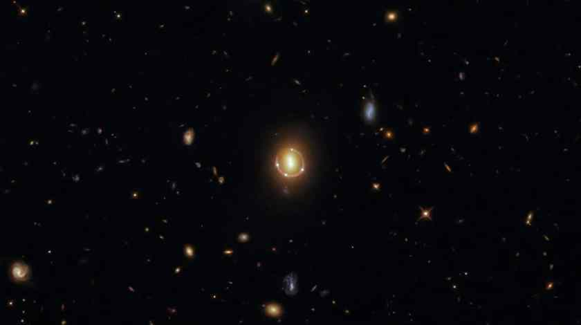 Image shows the gravitational lens effect predicted by Albert Einstein, photographed by Hubble.  The photo shows four points of light circling another two points centered, but it's actually just three bodies