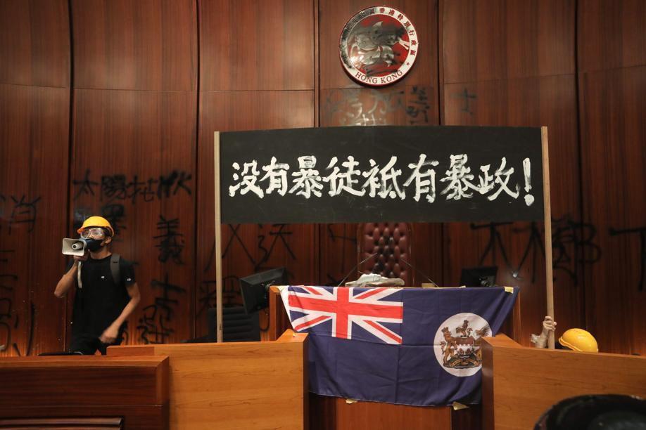 1er juillet 2019: Des manifestants hostiles au gouvernement pro-Pékin ont envahi l'hémicycle du Parlement de Hong Kong et y ont déployé le drapeau colonial britannique après avoir forcé l'entrée du bâtiment.
