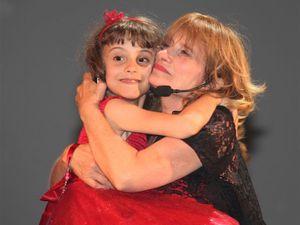 """En rouge, dans les bras de sa mamie, c'est la petite fille de la gagnante """"Bernadette Cremades"""". Cette petite fille, autiste, a récité un texte très émouvant pour sa Mamie. Comme la plupart des """"super mamies"""" Bernadette Cremades est engagée dans la vie associative, et en l'occurrence elle s'occupe d'enfants ayant un handicap. A droite  la chanteuse française ALICE DONA, qui elle, a été élue SUPER MAMIE à VIE"""