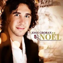 "Cover of Josh Groban's album ""Noel,"" which depicts Groban smiling slightly at the camera while surrounded by gold-toned holiday lights."
