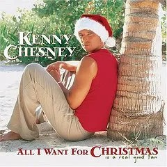 "Cover of Kenny Chesney's album ""All I Want For Christmas...Is a Real Good Tan,"" which depicts Chesney sitting on a beach while wearing a red tank shirt, khakis, and a Santa hat."