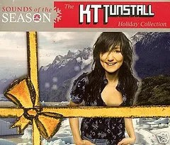 "Cover of KT Tunstall's album ""Holiday Collection,"" which depicts the singer standing outdoors and smiling. The image has been edited to include a yellow ribbon on top of the photograph."