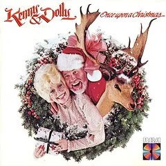 "Cover of Dolly Parton and Kenny Rogers' album ""Once Upon a Christmas,"" which depicts Dolly Parton and Kenny Rogers smiling while surrounded by a large Christmas wreath. They stand next to a reindeer with large antlers."