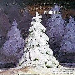 "Cover of Mannhein Steamroller's album ""Christmas in the Aire,"" which depicts a snow-covered fir tree in an outdoor environment."