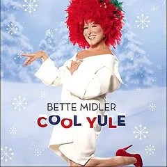 "Cover of Bette Midler's album ""Cool Yule,"" which depicts Midler standing happily in a snowy environment; she wears a white dress and a very large hat that appears to be made from red flowers."