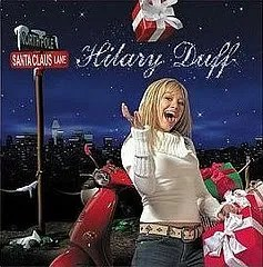 Cover of Hilary Duff's holiday album, which depicts the singer standing outside and next to a large sleigh while smiling happily. A wrapped gift floats above her head.