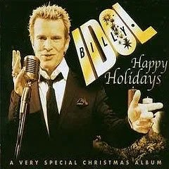 "Cover of Billy Idol's album ""Happy Holidays: A Very Special Christmas,"" which depicts a be-suited Billy Idol singing into a microphone and pointing at something out-of-frame."