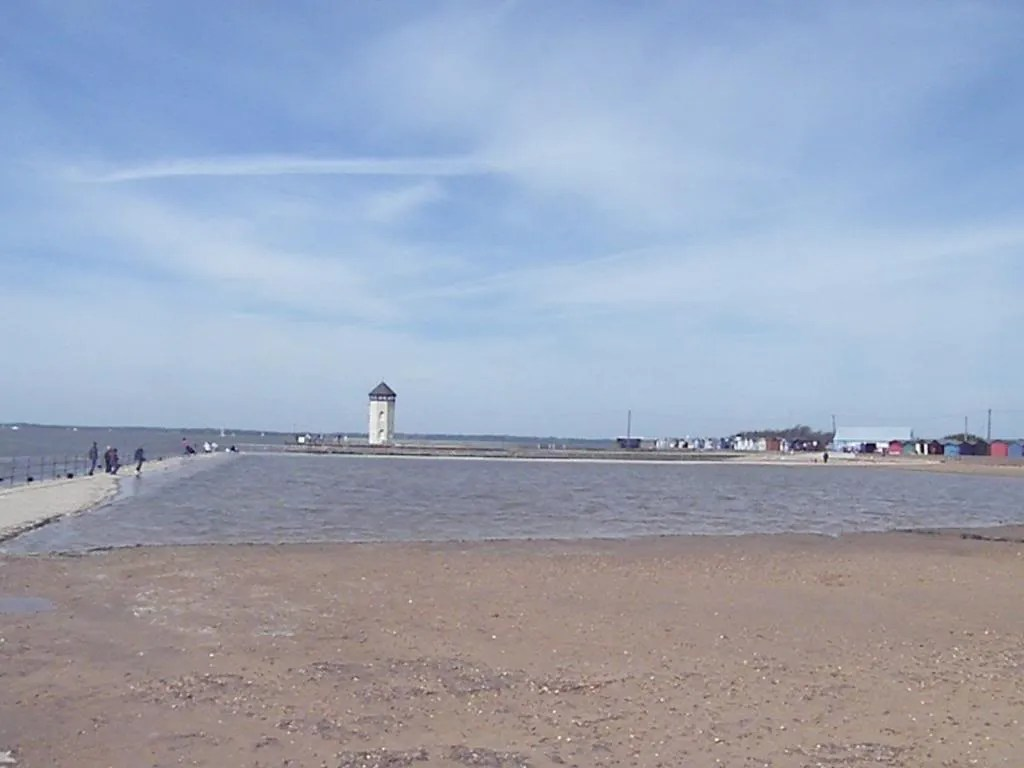 A photo depicting a shallow swimming pool separated from the sea by a low wall. There is a lighthouse in the distance