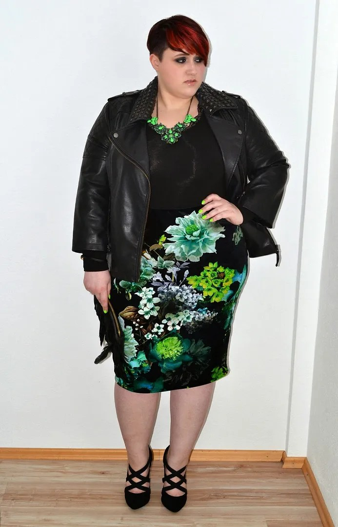 plus size outfit with black leather jacket, black top, and black skirt with neon green floral print