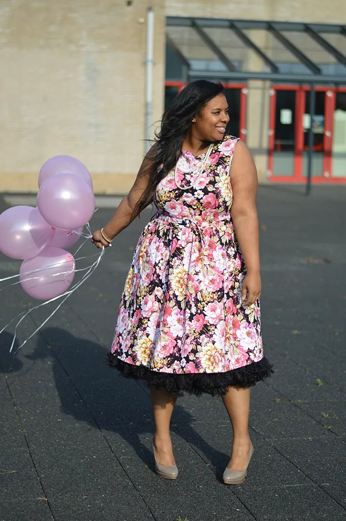 plus size outfit with pink and black floral dress, black petticoat, and pink balloons
