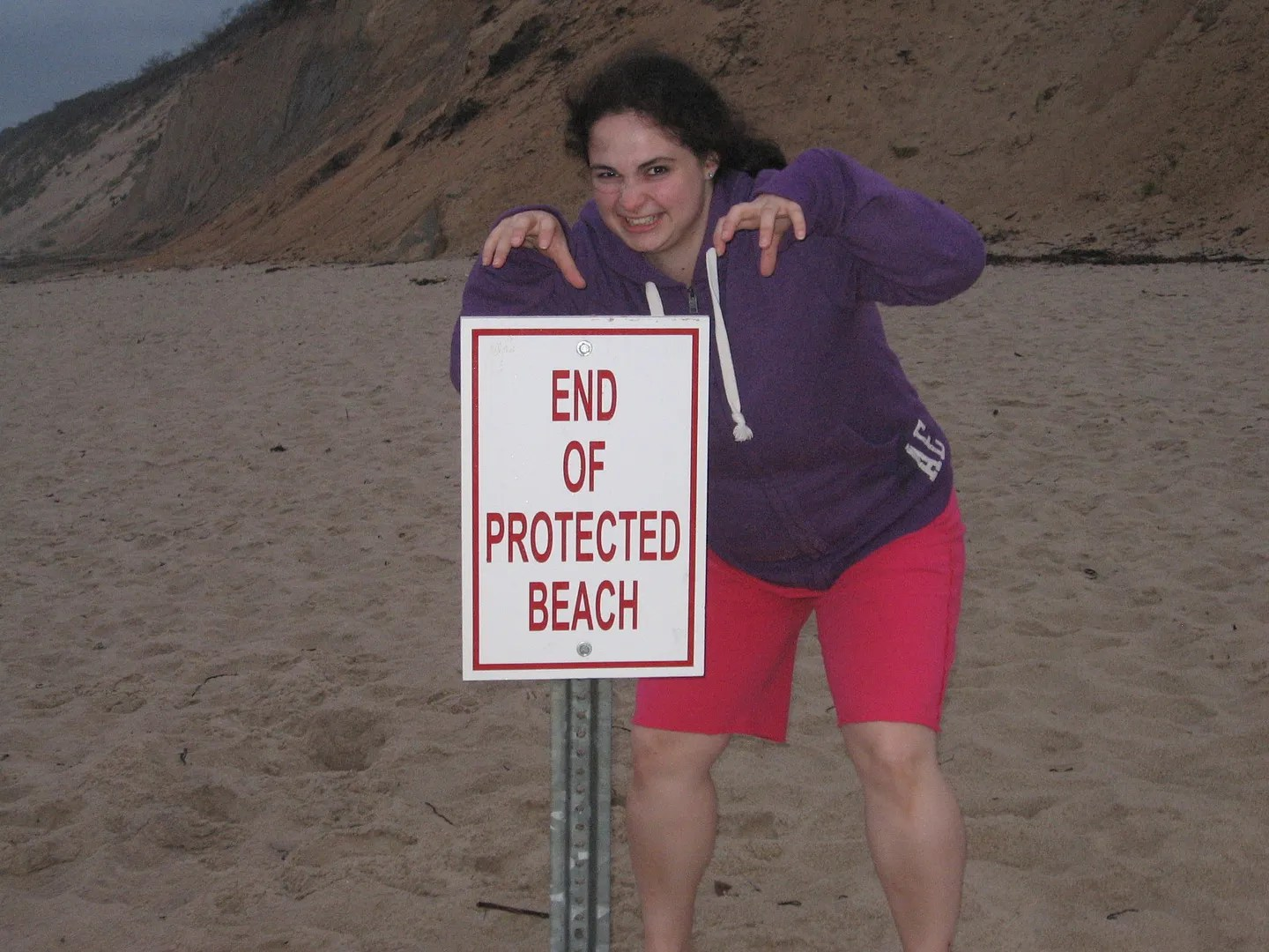 woman creeping behind sign on beach that says