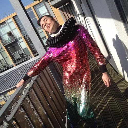 guy wearing rainbow sequin dress with black ruffled collar