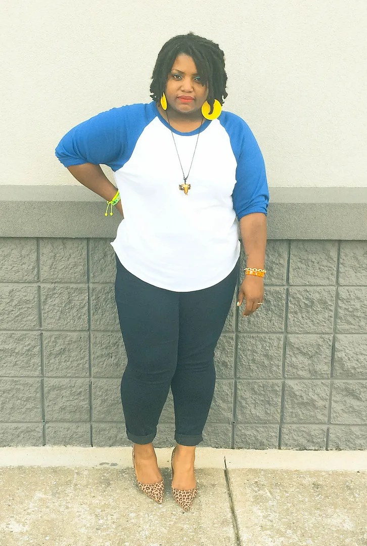 plus sizewoman wearing black pants, blue and white baseball tee, and yellow earrings