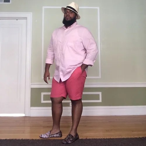 plus size man wearing light pink button down shirt and dark pink shorts