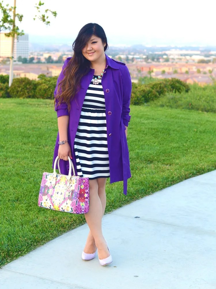 plus size outfit with black and white striped dress, purple coat, floral bag